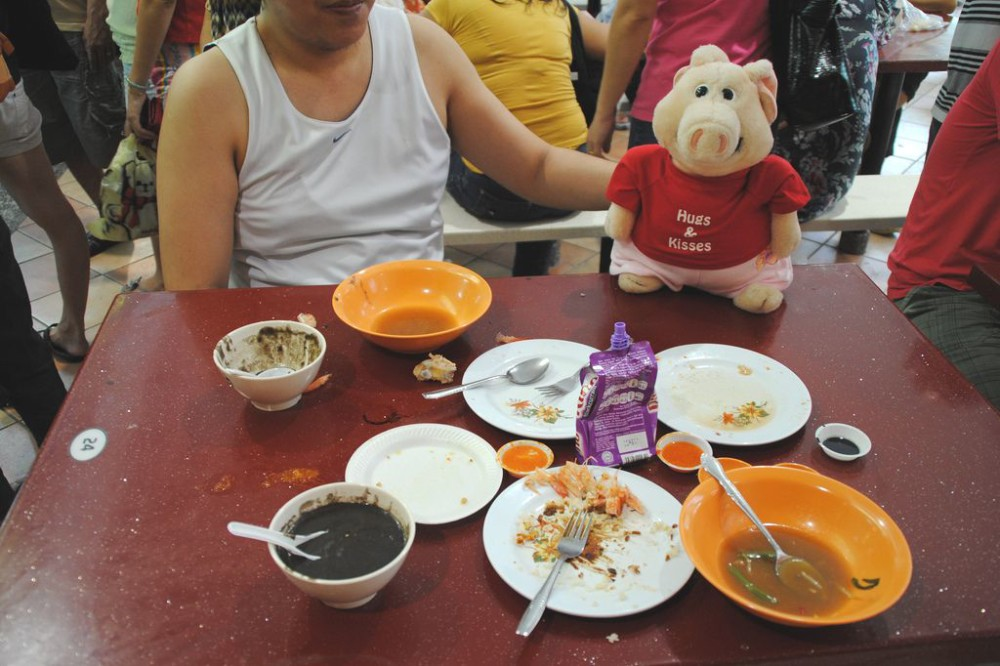 A stuffed pig sitting in front of several different food in Singapore.