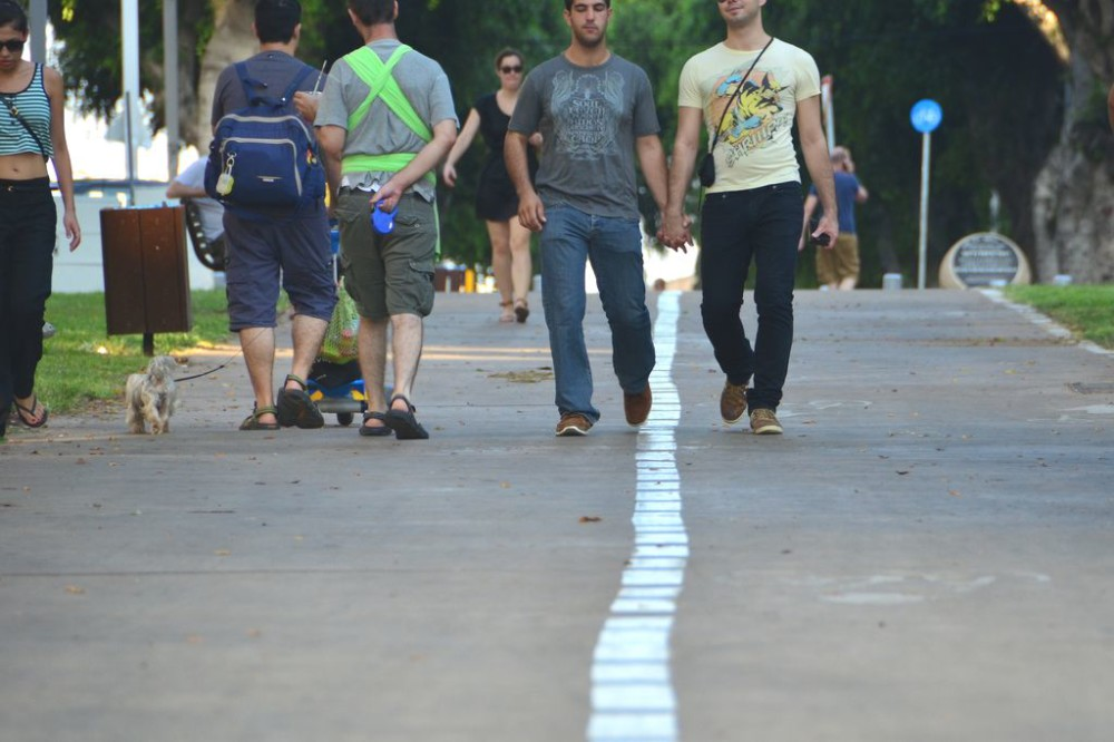 Gay couple holding hands on Ben Tsion Boulevard in Tel Aviv, Israel