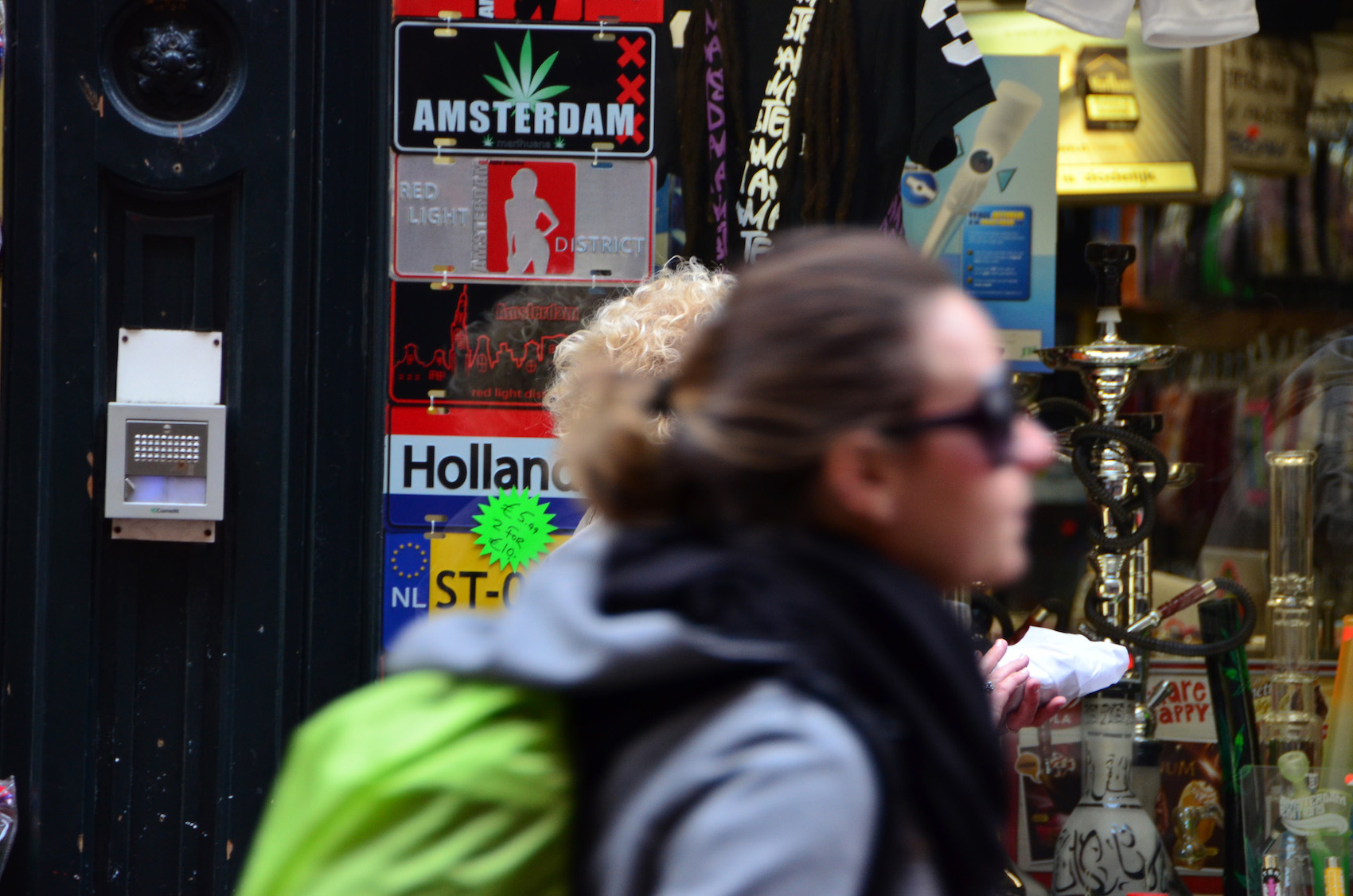 A tourist passes in front of a coffee shop in Amsterdam