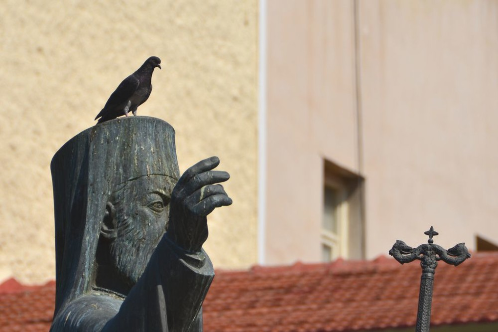 Bird perched on top of Greek Orthodox statue in Athens, Greece