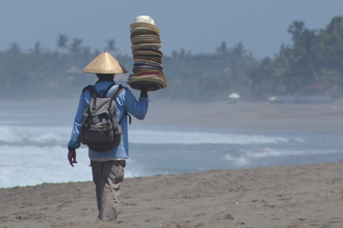 Beach Vendor Selling Hats Long Term Travel and Spending Habits