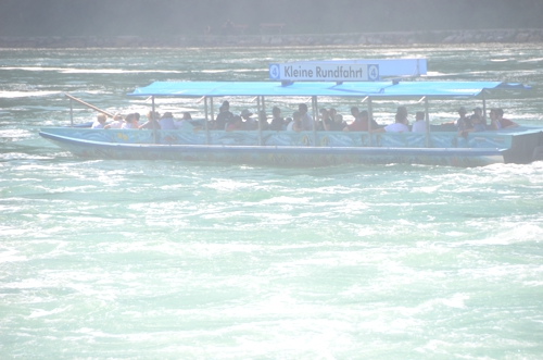The boat is shrouded in mist, even as it sits relatively far away from Rheinfall